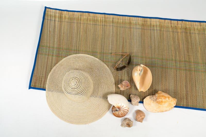 Hatten, solglasögon och skalen på en färgrik filt på isolerad vit bakgrund royaltyfria bilder