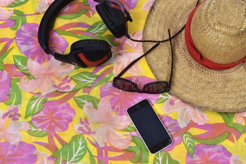 Hattexponeringsglas mobiltelefon och hörlur över den mönstrade torkduken arkivbilder
