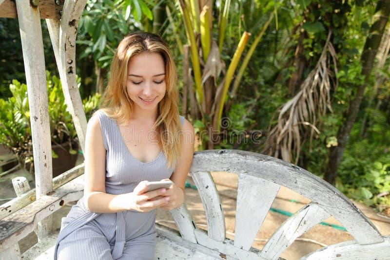 hatting由有棕榈的智能手机的年轻愉快的妇女在背景中,坐摇摆 免版税图库摄影