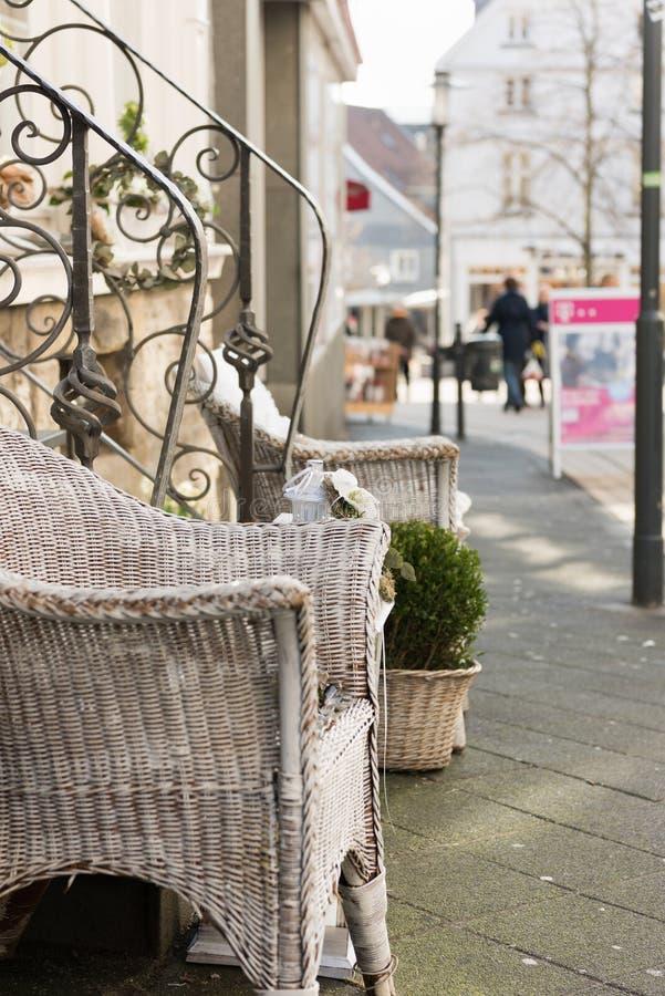 HATTINGEN, ΓΕΡΜΑΝΊΑ - 15 ΦΕΒΡΟΥΑΡΊΟΥ 2017: Οι άσπρες χρωματισμένες υφαμένες καρέκλες ιτιών και οι πράσινες εγκαταστάσεις διακοσμο στοκ φωτογραφία με δικαίωμα ελεύθερης χρήσης