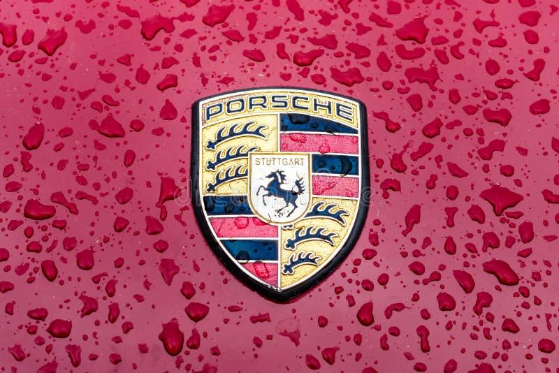 Haubenemblem des Sportautos Porsche in den Regentropfen auf dem Burgunder-Hintergrund stockbilder