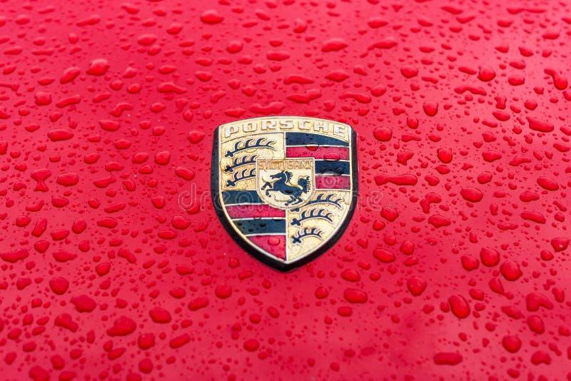 Haubenemblem des Sportautos Porsche in den Regentropfen auf dem roten Hintergrund lizenzfreie stockbilder