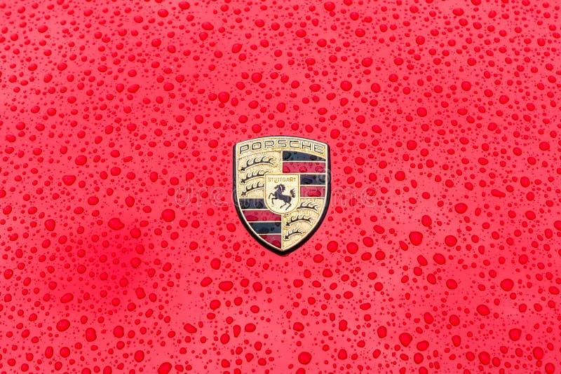 Haubenemblem des Sportautos Porsche in den Regentropfen auf dem roten Hintergrund stockfotos