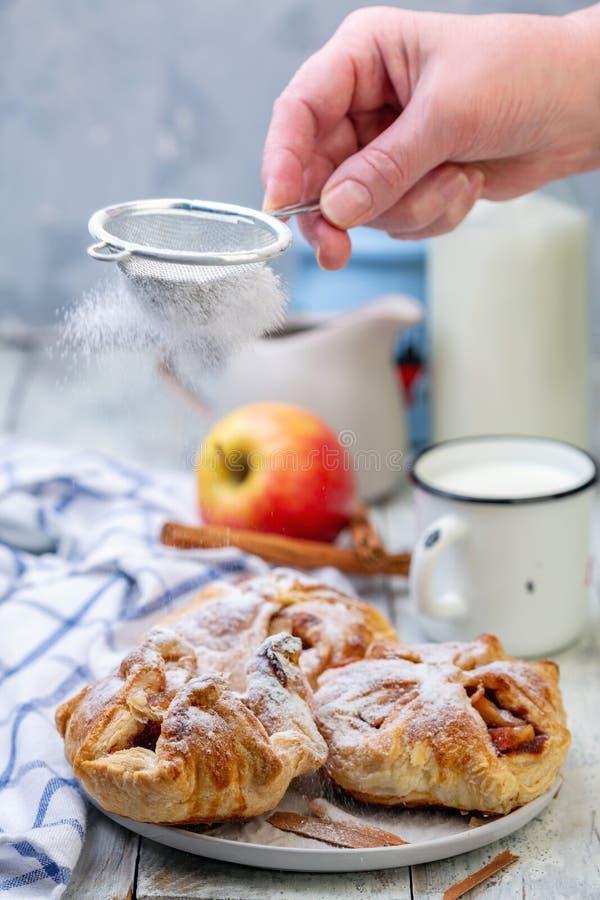 Hauche von Äpfeln und von Zimt auf einer Platte besprüht mit Puderzucker stockfoto