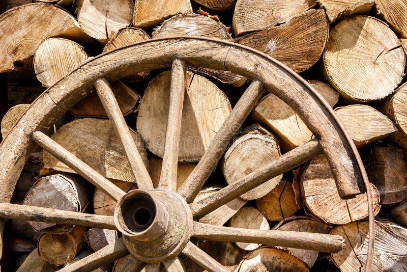 Haufen des Brennholzes und des alten gebrochenen Rades stockfotografie