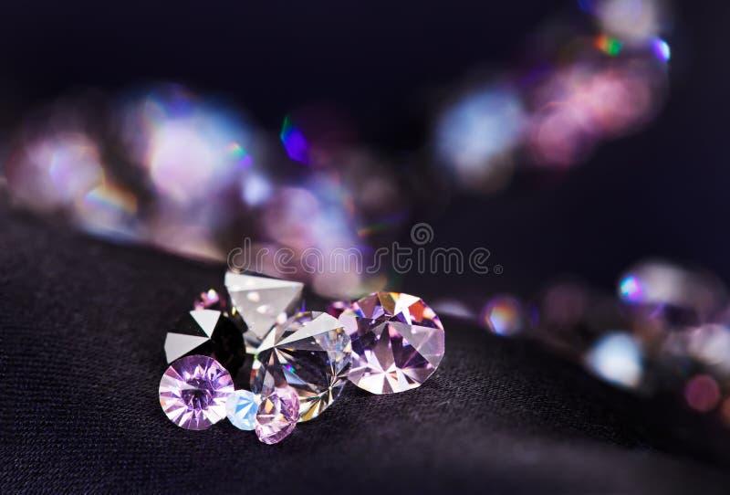Haufen des Diamanten (kleines purpurrotes Juwel) über schwarzer Seide stockbilder