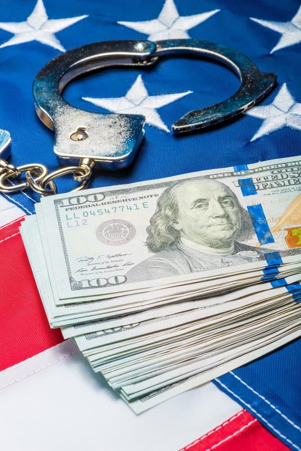 Haufen des Geldes und der Handschellen auf Abschluss der amerikanischen Flagge oben lizenzfreies stockfoto