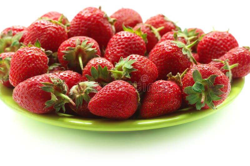 Haufen von Erdbeeren in der gr?nen Platte stockfotos