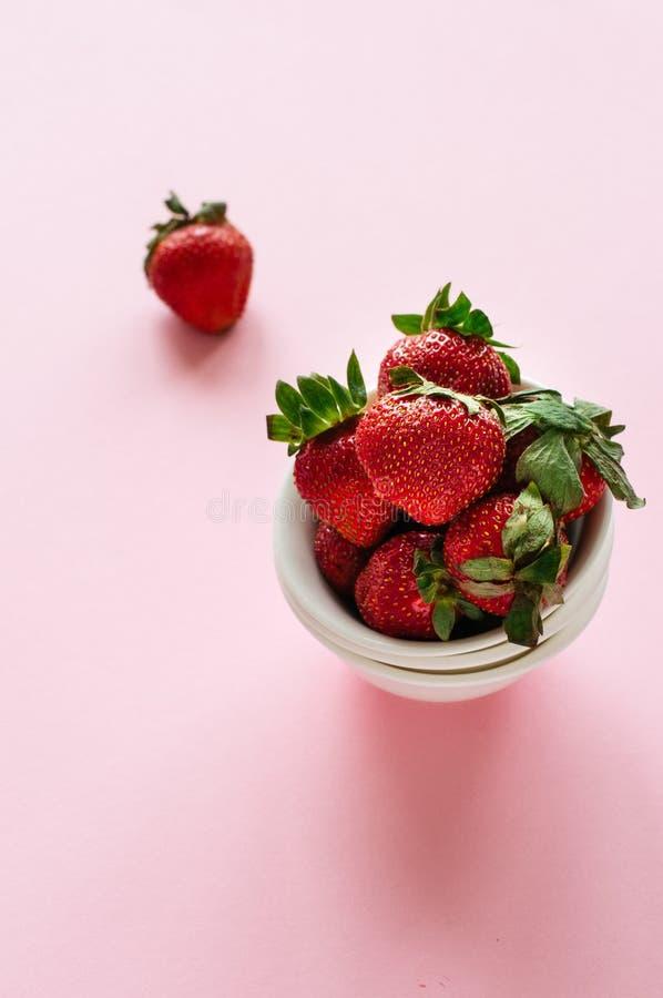 Haufen von frischen reifen Erdbeeren in einer weißen Schüssel auf einem rosa backgr lizenzfreie stockbilder