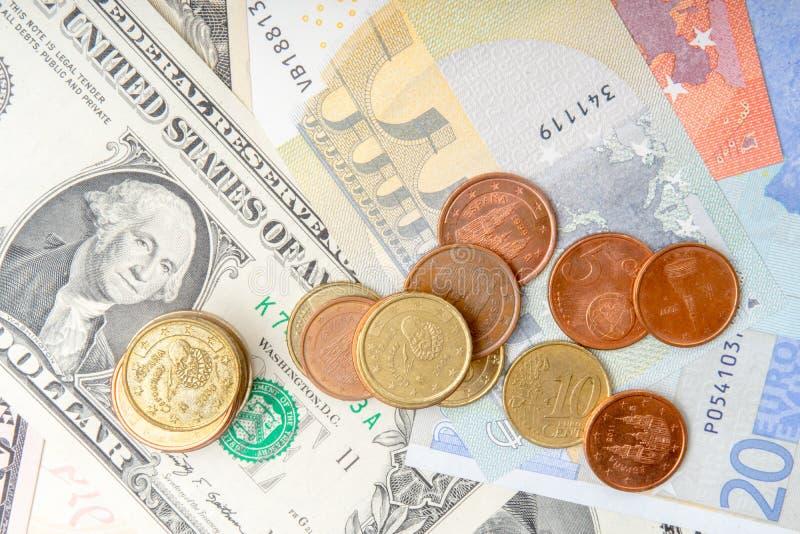 Haufen von Münzen auf Hintergrund des verschiedenen Euros und der Dollarbanknoten stockbilder