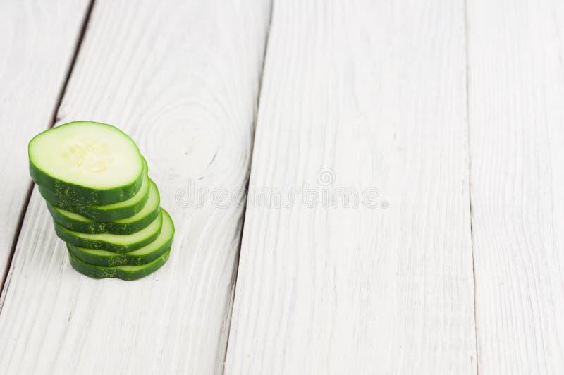 Haufen von Scheiben der frischen grünen Gurke auf rustikalen hölzernen Planken stockfotografie