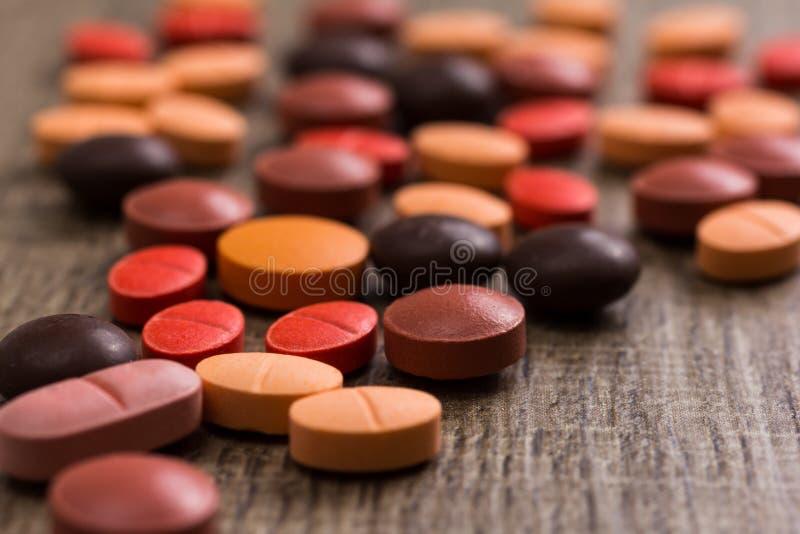 Haufen von sortierten orange, braunen und roten Kapseln auf Holztisch lizenzfreie stockfotos