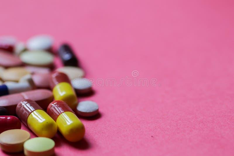 Haufen von Tabletten und von Kapseln im rosa Hintergrund mit Raum für den Text selektiv fokussiert lizenzfreies stockbild