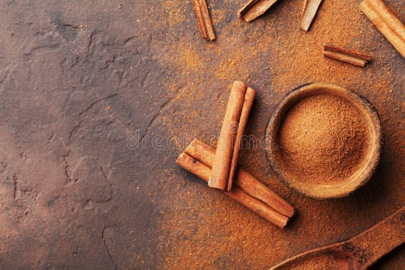 Haufen von Zimtstangen und von Pulver auf Draufsicht des braunen rustikalen Hintergrundes Aromatische Gewürze stockfoto