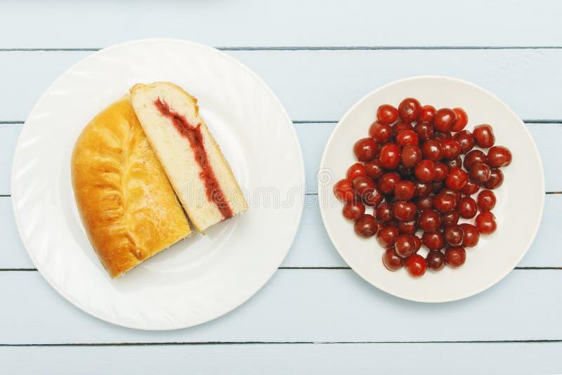 Haufenkirschen und Stücktorte auf Holztisch Beschneidungspfad eingeschlossen Gesundes Nahrungsmittelkonzept lizenzfreie stockfotografie