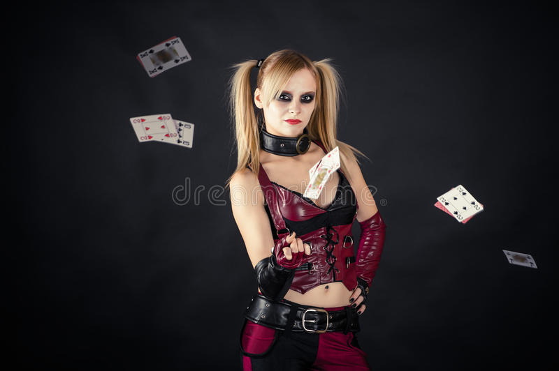 Haughty harlequin throws cards royalty free stock photos
