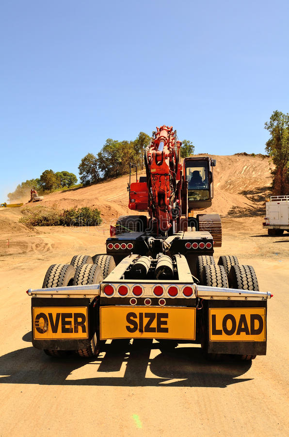 Haul Excavator. Large track excavator being delivered to a construction site on a low-boy trailer and truck stock photography