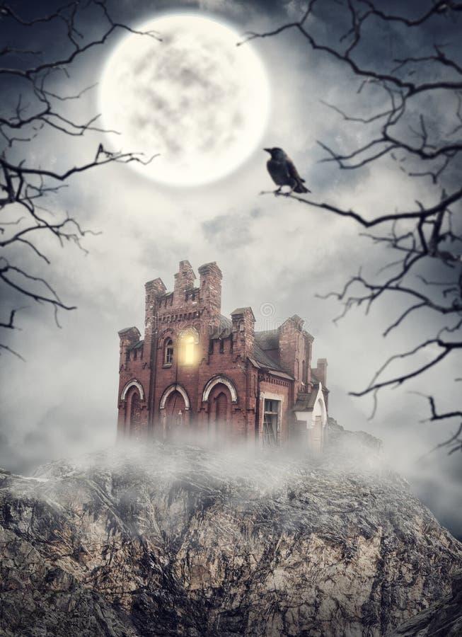 Haunted покинуло дом на утесе против летучих мышей полный halloween преследовал место тыквы луны дома стоковые фото