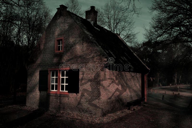 Haunted house. Spooky house with shadows on the wall in the middle of a dark forest stock photography