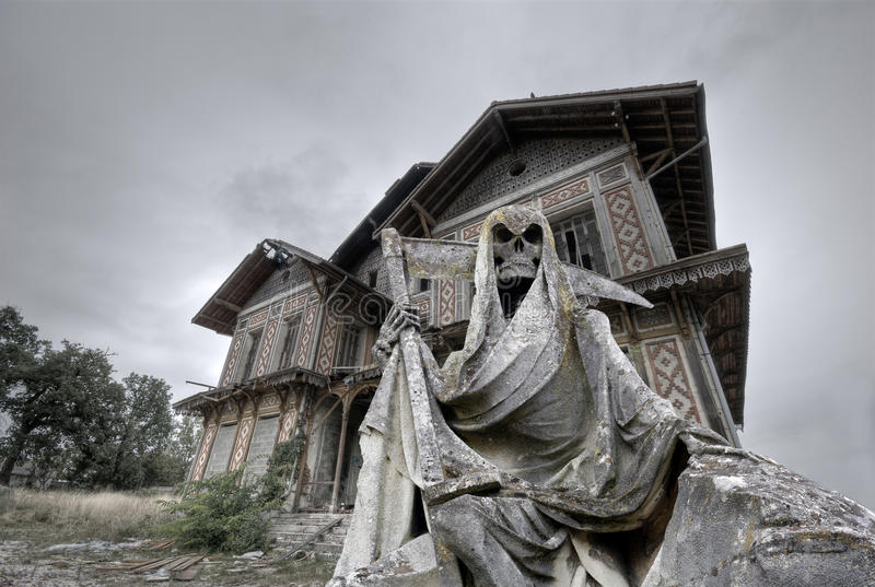 Haunted house. Abandoned and ruined manor with a gream reaper statue in foreground stock photo