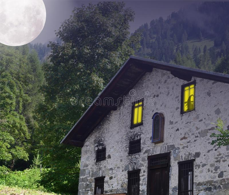 Haunted house in the woods, with moon in the sky. stock image