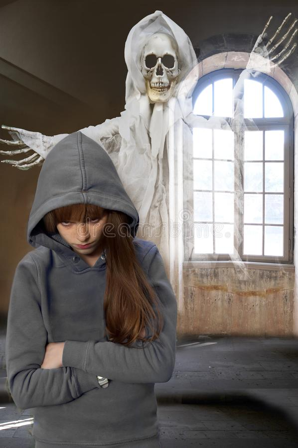 In a haunted mansion, nightmare of a teenage girl. Scary horror scene. Ghost behind a teenage girl in empty room of an old haunted castle royalty free stock image