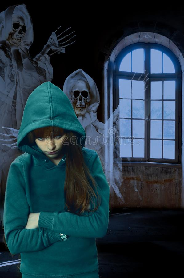 In a haunted mansion, nightmare of a teenage girl. Scary horror scene. Ghost behind a teenage girl in empty room of an old haunted castle royalty free stock photography