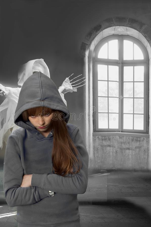 In a haunted mansion, nightmare of a teenage girl. Scary horror scene. Ghost behind a teenage girl in empty room of an old haunted castle stock images