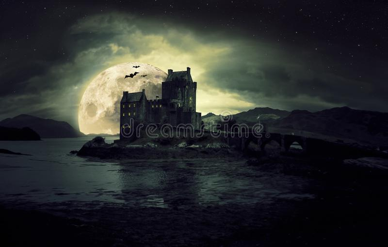 Haunted mystic eerie Eilean Donan Castle in Scotland with the sea around it dark clouds and the moon. Dark haunted mystic eerie Eilean Donan Castle in Scotland royalty free stock images