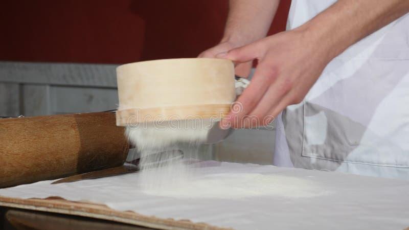 Haupt-` s übergibt das Sieben des Mehls durch ein Sieb für das Backen lizenzfreie stockfotos