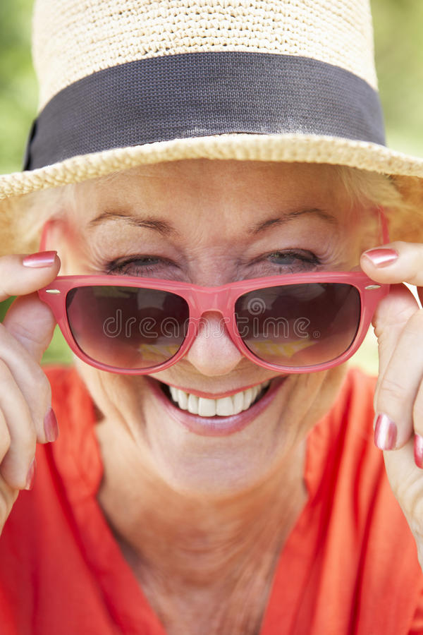 Haupt- und Schulter-Porträt der lächelnden ältere Frauen-tragenden Sonnenbrille stockbild