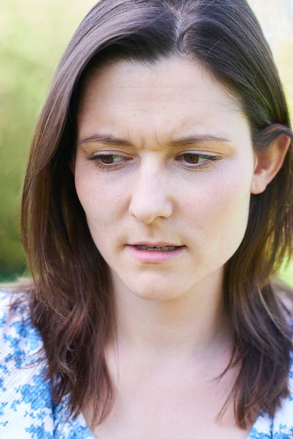 Haupt- und Schulter-Porträt im Freien der besorgten jungen Frau stockfoto