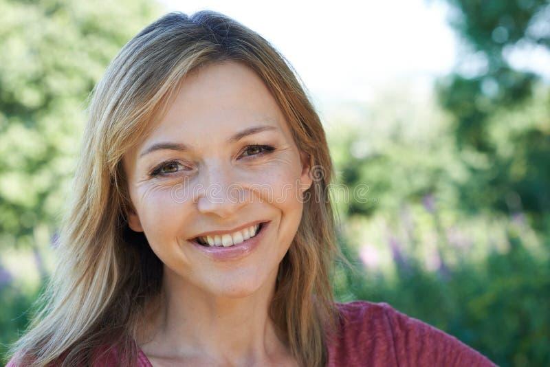 Haupt- und Schulter-Porträt im Freien der lächelnden reifen Frau stockbild