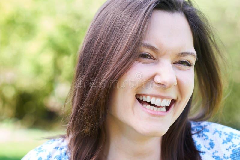 Haupt- und Schulter-Porträt im Freien des Lachens der jungen Frau lizenzfreies stockbild