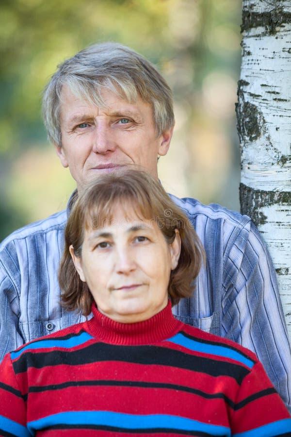Haupt- und Schulterporträt von zwei kaukasischen Pensionären, die zusammen nahe Birke, Mann umfasst seine Frau stehen Fokus auf m stockfotografie