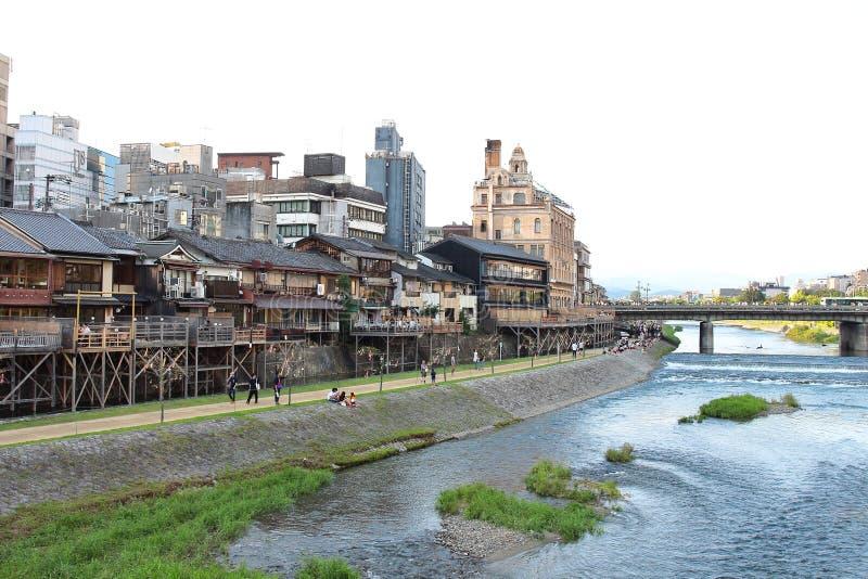 Hauptansicht der Kamo-Flusspromenade mit vielen Terrassen von Restaurants und der Bars mit Kyoto-` s alten Stadtgebäuden auf Hint lizenzfreies stockfoto