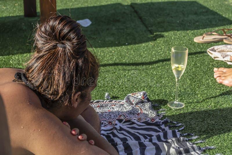 Hauptansicht der Mulattefrau liegend auf Stoff, nehmend auf Gras, mit Glas des Getränks ein Sonnenbad stockfotografie