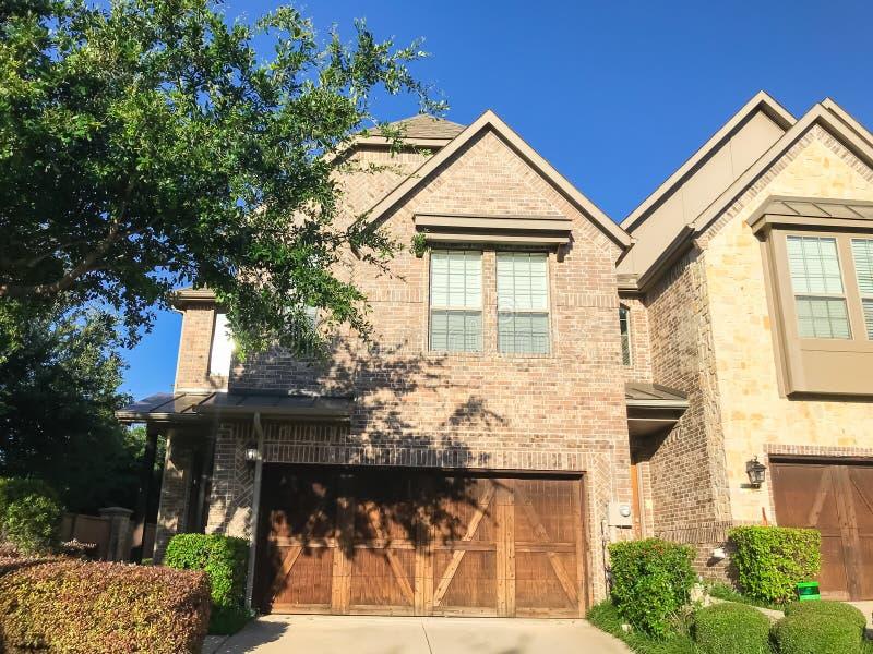 Haupteingang des nagelneuen Hauses mit h?lzernen Garagentoren nahe Dallas, Texas lizenzfreie stockbilder
