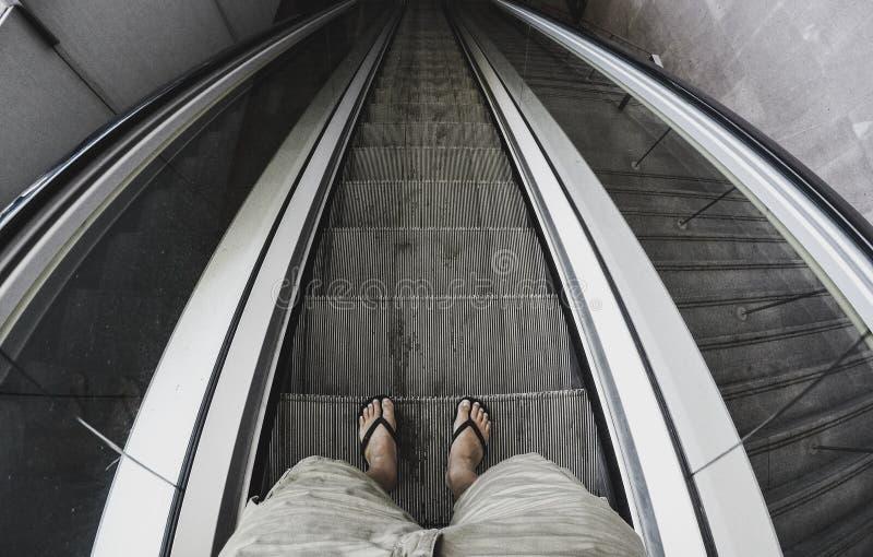 Hauptgesichtspunkt des stehenden Mannes mit unten auf die Aufzug staris zu einem schwarzen Untergrund barfuß gehen - Konzept von  lizenzfreies stockbild