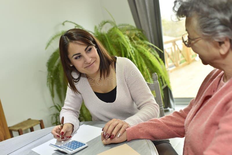 Haupthelfer, der um Schreibarbeit der älteren Frau sich kümmert lizenzfreies stockfoto
