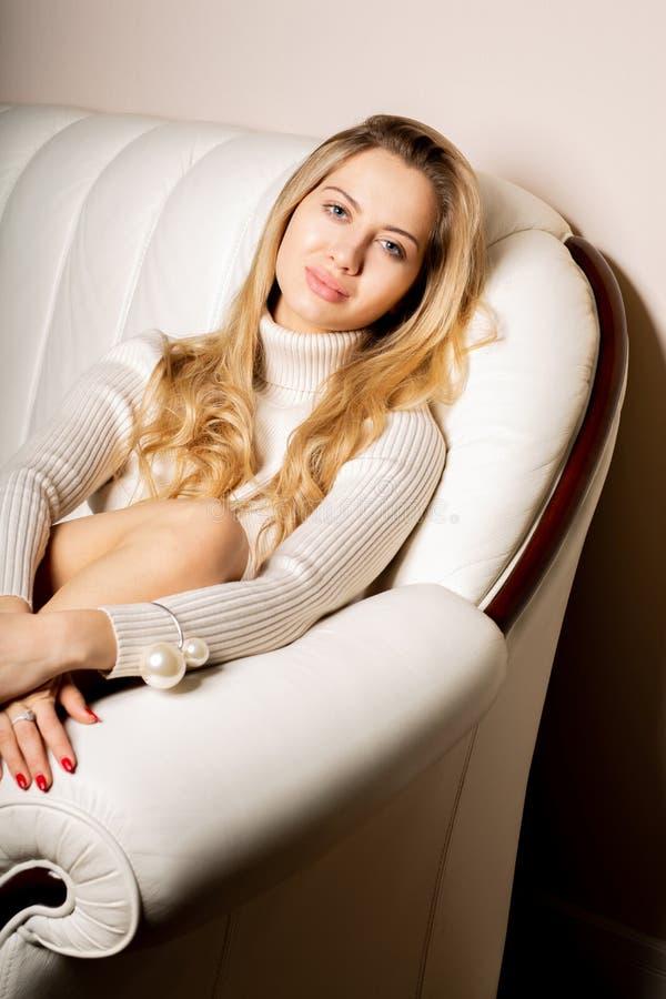 Hauptlebensstilporträt der tragenden Strickjacke der reizenden Frau, entspannend auf Sofa am Wohnzimmer stockfotos