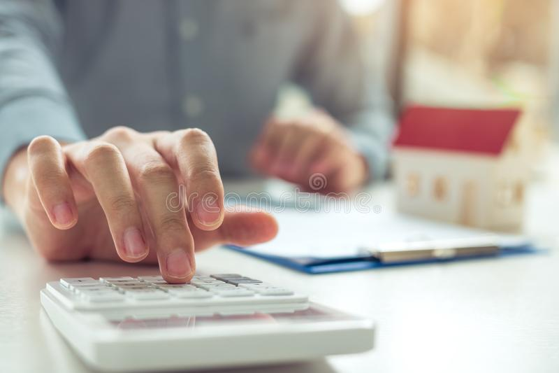 Hauptmittel benutzen einen Taschenrechner, um die Kreditlaufzeit jeden Monat zu berechnen für den Kunden stockfotos