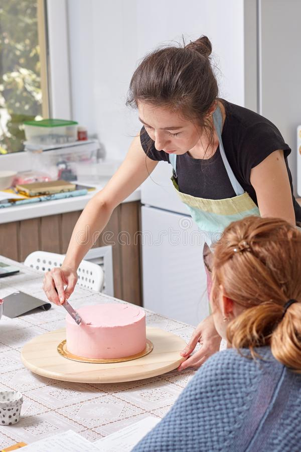 Hauptpatissier unterrichtet, wie man einen Kuchen mit Sahne planiert stockfotos