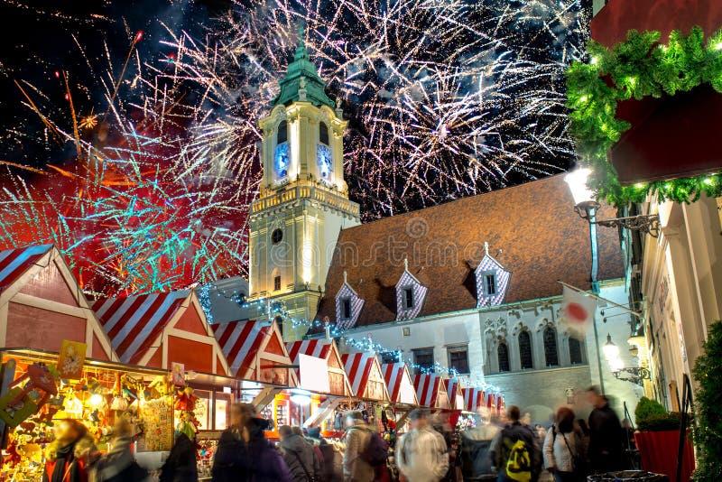 Hauptplatz in der Nacht in Bratislava, Slowakei während der Weihnachtsmarktzeit mit großem Feuerwerk auf der Rückseite lizenzfreies stockfoto