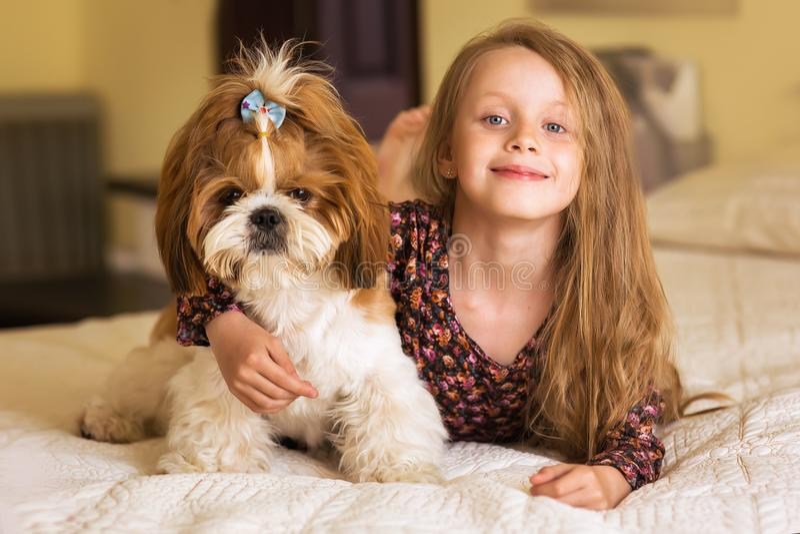 Hauptporträt des netten Kindes umarmend mit Welpen des Hundes auf dem Sofa lizenzfreie stockbilder
