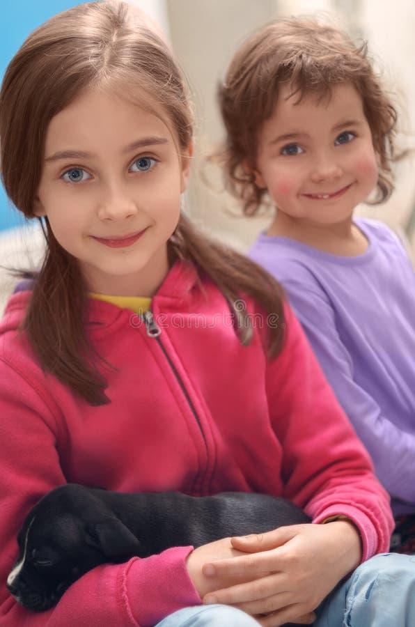 Hauptporträt von zwei netten lächelnden kleinen Mädchen mit Schlafenwelpen lizenzfreie stockfotos