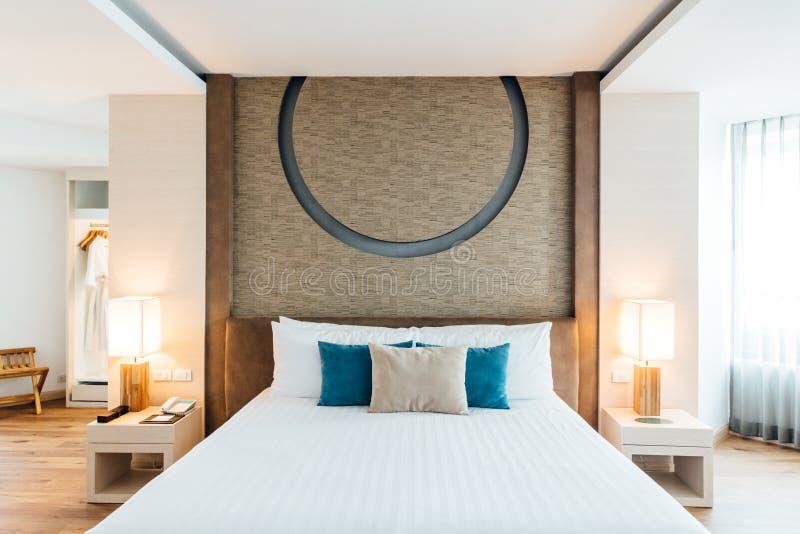 Hauptschlafzimmer verziert mit hellem und warmem Ton, weißen Decken-, Blauen und Grauenkissen lizenzfreie stockbilder