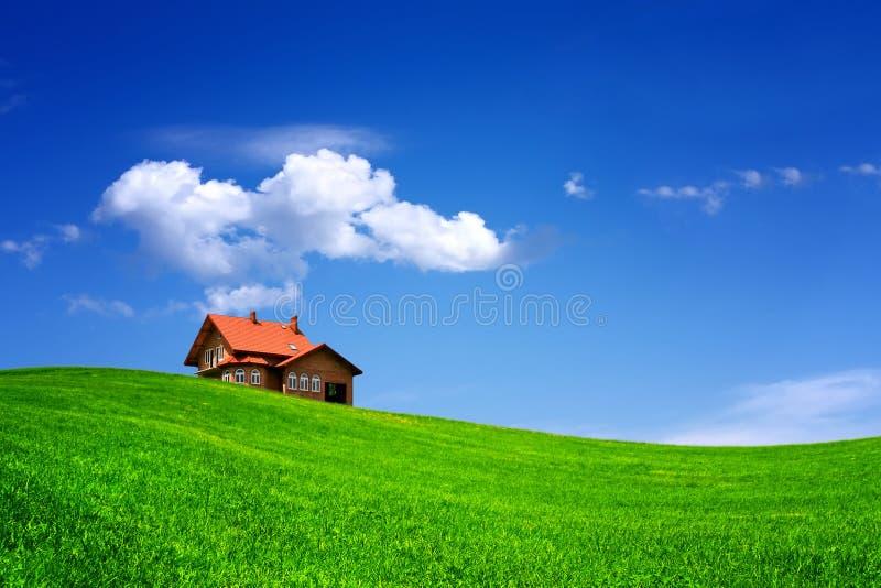 Haus auf grünem Feld lizenzfreies stockfoto