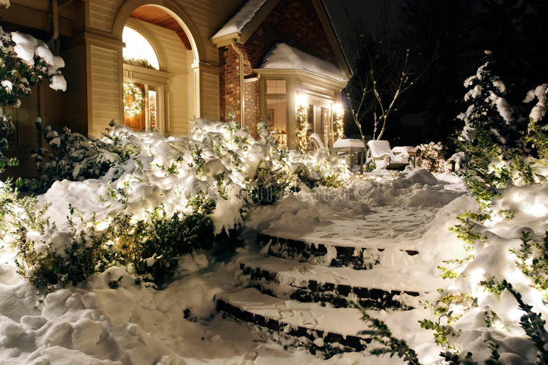 Haus auf schneebedeckten Nachtweihnachtsleuchten stockfotos