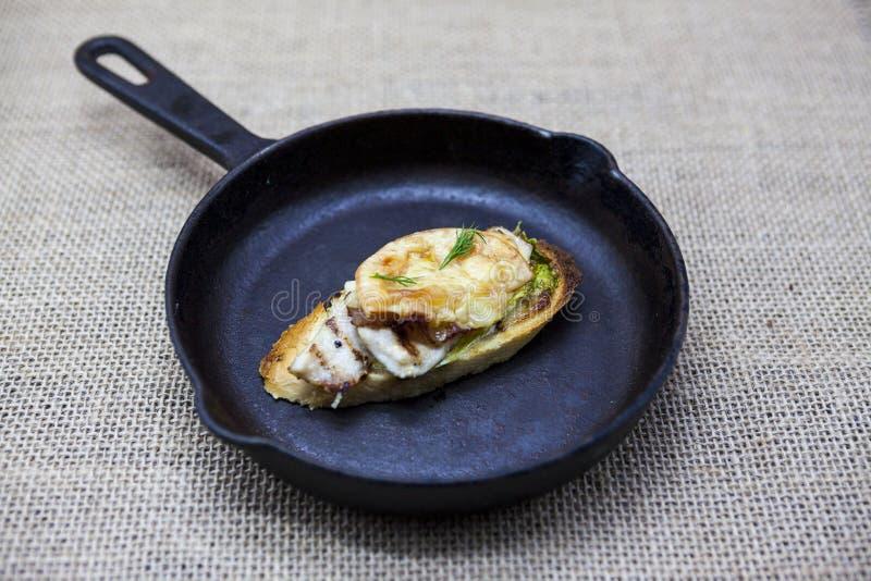 Haus backte heißes Sandwich mit Hühnerkäse, Zwiebel, Paprikapfeffer, Knoblauch auf einer Gusseisenwanne auf einem Textilhintergru lizenzfreies stockbild